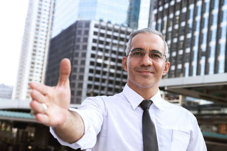 confident success businessman professional making handshake in front of office building at business center in the city after giving opportunity for new partner. business and partnership concept.