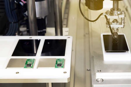automatic robot arm with vacuum sucker working in the production line and assembling smartphone screens in the new innovative and high technology smartphone factory with sunbeam.