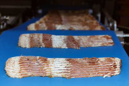 raw rasher bacon slide ready to pack in packaging on conveyor belt of automation meat slide machine in the food factory. manufacturing machinery and food  industry concept