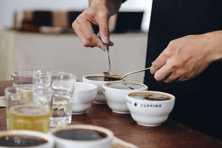 professional Q Grader preparing to test and inspecting the quality of coffee and skim off the coffee grounds from ceramic cup on the table. film style photo.