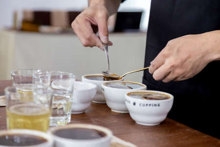 professional Q Grader preparing to test and inspecting the quality of coffee and skim off the coffee grounds from ceramic cup on the table. 写真素材
