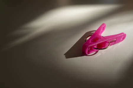 pink plastic cloth clip on the floor with light, shade and shadow from the window with copy space.