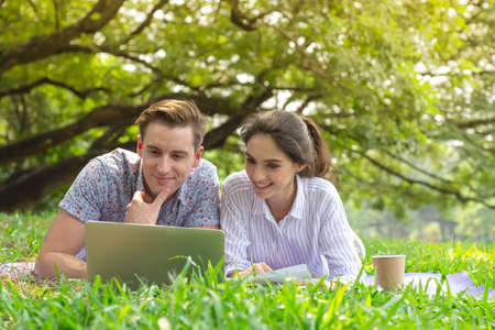 smiling young man and woman couple using computer to searching for information for weddings, honeymoon travel. Stock Photo