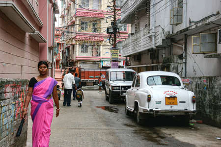 Kolkata, India - October 1, 2020 : indian woman in sari or saree traditional dress walking to work with father holding child hand to go to school on monday in Kolkata. simple life in India morning Redakční