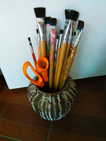 Paintbrushes and a scissor in a pottery photo