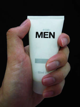bath treatment: Hand holding a package of men s skincare product Stock Photo