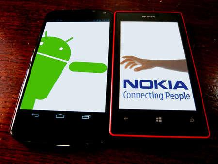 Main logo de parodie de Nokia. Nokia tendre la main à Android. Google Nexus 4 et Nokia Lumia 520 sur fond de bois Banque d'images - 21008615