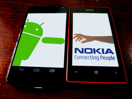 Nokia s hand logo parody. Nokia reach out to Android. Google Nexus 4 and Nokia Lumia 520 on wooden background