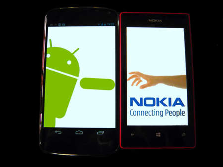 Nokia s hand logo parody. Nokia reach out to Android. Isolated picture of Google Nexus 4 and Nokia Lumia 520.