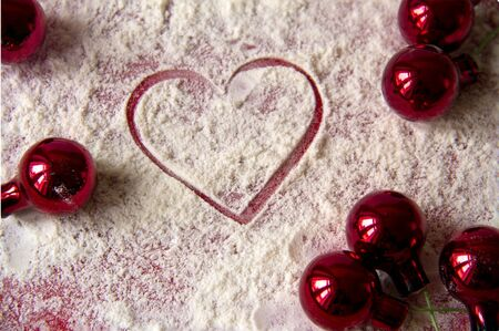 cutout heart  in sugar with red christmas decorations on red background