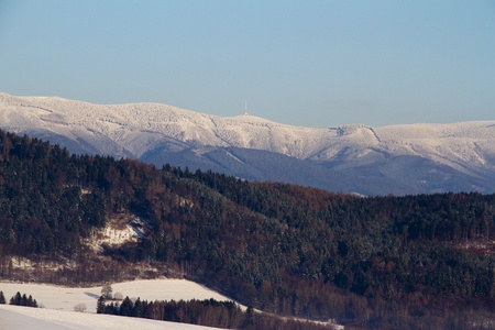 Winter landscape: panorama of Jeseniky mountains with watchtower on the highest top Praded
