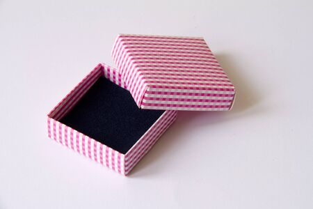 Opened small paper giftbox with black inner side on white background