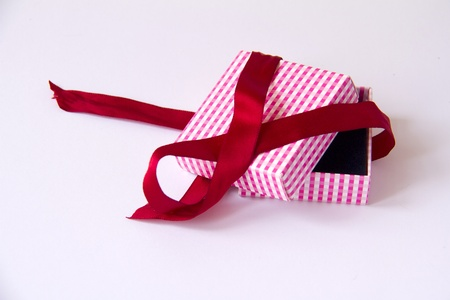 Opened small paper giftbox  with black inner side and untied red bow on white background Stock Photo