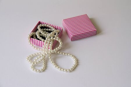 Small paper giftbox opened with pearl necklace