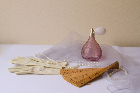 Vintage still life with gloves, fun and perfume bottle Stock Photo