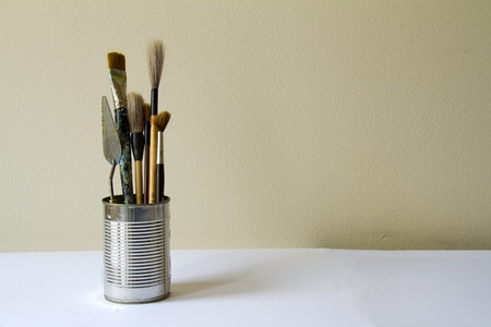 Artist´s still life - painting supplies in tin on light background