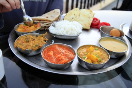 Traditional delicious north indian thali served in small metal bowls with rice and bread photo
