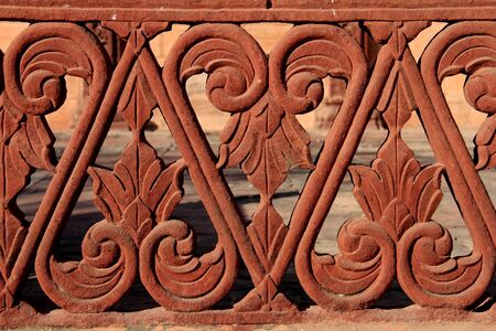 Red sandstone balustrade detail with floral and geometric elements, India