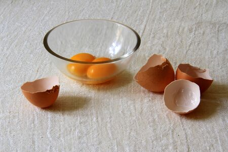 Still life with egg yolks in glass bowl and eggshells on the table