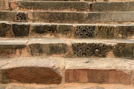 fragments: Steps of old, worn stone stairs with recycled decorative fragments