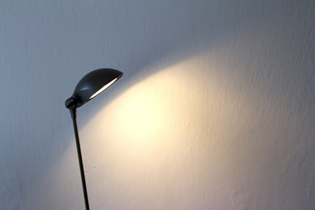 Office lamp with light on against white wall, cropped Stock Photo