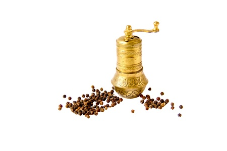 Oriental brass pepper mill and black peppers isolated on white background