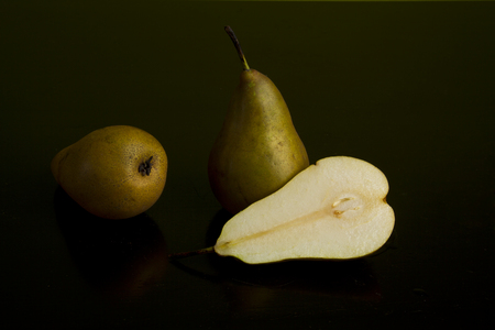 composition of two whole pears and sliced pear on dark background Stock Photo