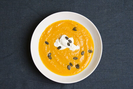 Plate of pumpkin soup with cream on blue textile background Stock Photo