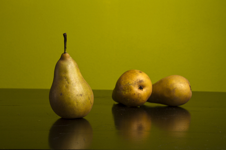 composition of three pears on green background Stock Photo