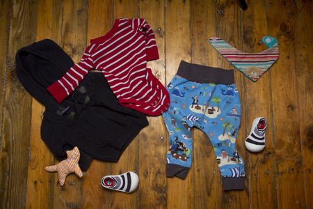 Group of baby clothing: knitted sweater, stripped  , barefoot shoes, trousers and toy cat on grunge wooden background. Top view