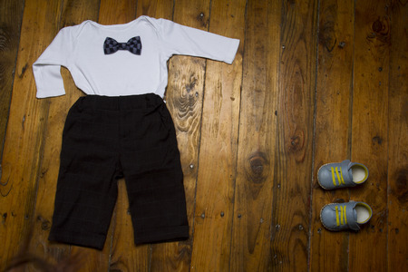 Group of baby clothing: white  , shoes, trousers and bow tie on grunge wooden background. Top view