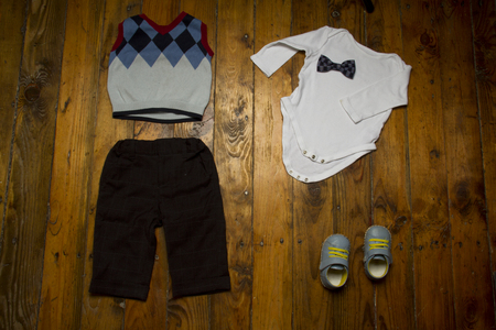 Group of baby clothing: white  , shoes, trousers, vest and bow tie on grunge wooden background. Top view
