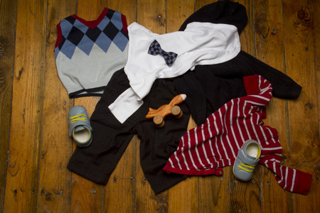 Group of baby clothing: knitted sweater,  , barefoot shoes, trousers, bow tie and toy cat on grunge wooden background. Top view Stock Photo