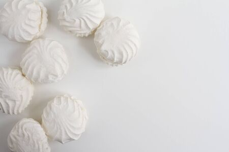 Symmetrical group of typical latvian marshmallow like sweets called zefiri. High key top view image on white background