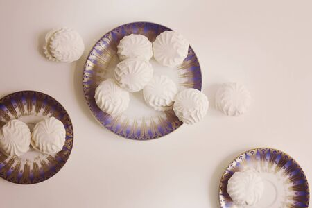 Group of typical latvian marshmallow like sweets called zefiri. Top view of zefiri on porcelain plates with vintage filter