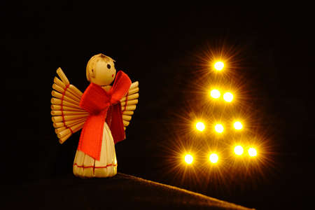 Little straw angel with shiny star tree Stock Photo