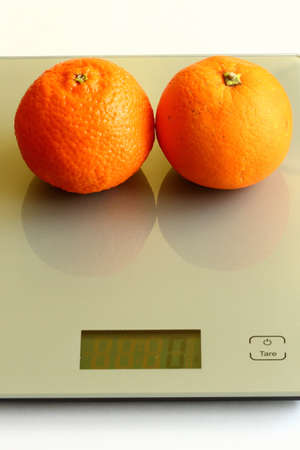 Pair of fresh orange and mandarine on a scale