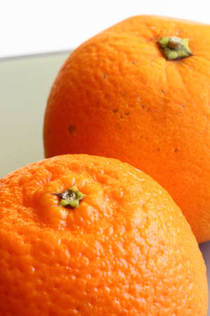 Pair of fresh orange and mandarine in closeup