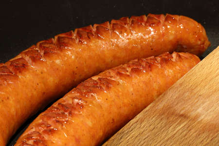 Pair of pork sausages in a pan Stock Photo