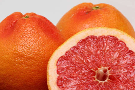 half cut red grapefruit with two others Stock Photo