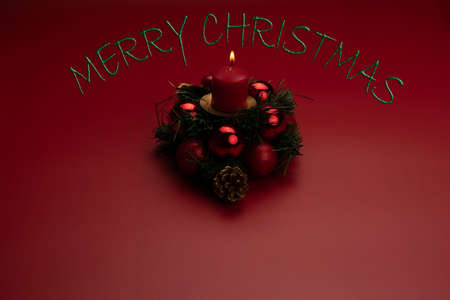 Christmas centerpiece with a candle over red background Фото со стока