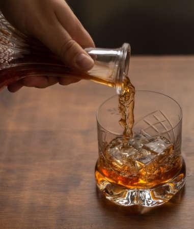 Serving a glass of whiskey Фото со стока