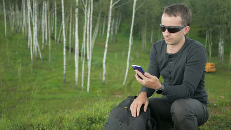 Young man in sunglasses pulls the phone out of the bag and talking. Against the background of beautiful nature: green trees and grass.