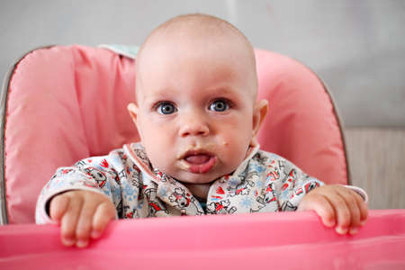 six month old: Beautiful baby eats porridge from moms hand. He is sitting on a pink childrens chair