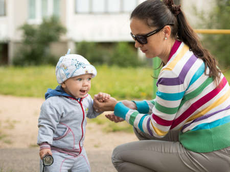 Beautiful baby boy playing on the playground with her mother. The boy is dressed in a light bike.