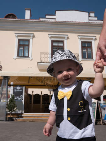 toddler walking: Beautiful toddler walking with his mother on a city holiday. Kid stylishly dressed with a butterfly and a cap. Stock Photo