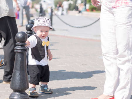 stylishly: Beautiful toddler walking with his mother on a city holiday. Kid stylishly dressed with a butterfly and a cap. Stock Photo