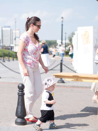 Beautiful toddler walking with his mother on a city holiday. Kid stylishly dressed with a butterfly and a cap. Standard-Bild