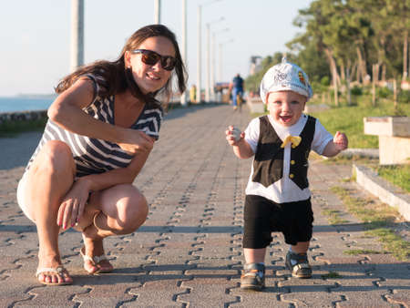 babysit: Mom and son playing near the ocean at sunset. In a very beautiful baby funny facial expression. Stock Photo