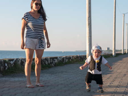 Mom and son playing near the ocean at sunset. In a very beautiful baby funny facial expression. Stock Photo